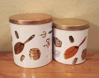 Set of 2 vintage Weibro nesting tin canisters with raised copper, silver and black kitchen gadgets all over.  Mid century kitchen canisters.