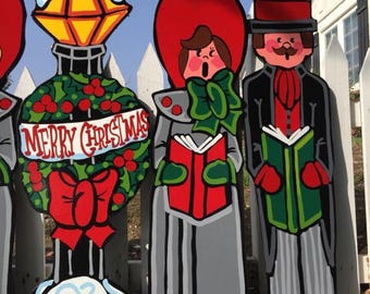Outdoor carolers with Merry Christmas lamp post signs