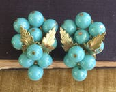 """A pair of Judith McCann """"wingback"""" grape cluster earrings with turquoise beads and gold foliate leaves"""