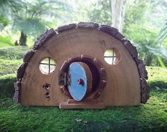 Rustic Wooden Hobbit house with Opening Blue Door and Bark Roof