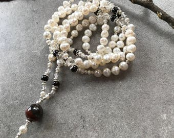 Mala of freshwater pearls and garnet, decorated with silver and rose quartz, end bead of tiger iron
