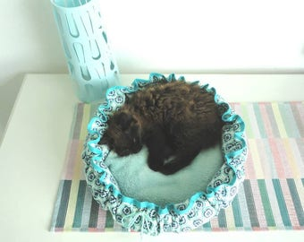 Cat bed in turquoise and white, of sturdy cotton with a soft cushion.