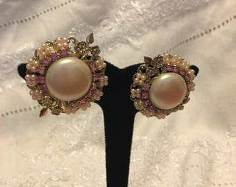 Delicate pink rhinestones and baby pearls showcase a large circular center Pearl with Flower adornments. Clip on earrings.