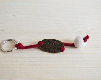 Red keychain with ceramic detail.