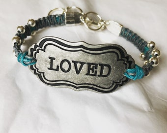 Loved metal bracelet on linen