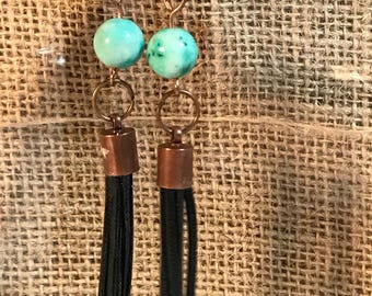Green glass bead and black leather tassel earrings.