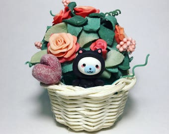 Mamegoma in skin of a cat in a basket with roses.