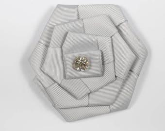 Grey fabric with a rhinestone flower