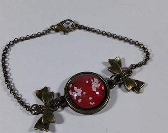 bronze bracelet with cherry blossoms on red background