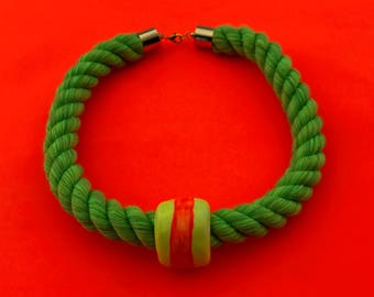 One bead necklace on green rope
