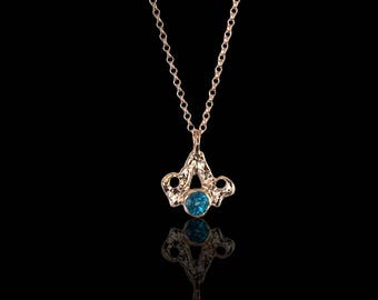Silver, minimalistic necklace with blue topaz on it