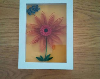Shadow box for baby nursery. Beautiful orange, red, quilled flower on mellon colored background. White plastic casing with plexi glass top.