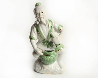Japanese Porcelain Mud Man Figurine ~ Vintage Asian Decor ~ White, Green, Gold trim ~ Man sitting w/ basket holding fish