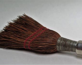 brown whisk broom with metal handle