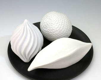 Three white carved porcelain pods on black tray