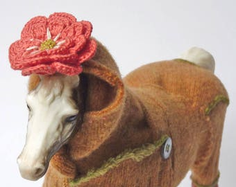 Altered figurine, model horse in sweater with flower and tassel, orange leg bad repair