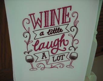 "Wine themed ""wine a little laugh a lot"" flour sack towel. Machine embroidered."