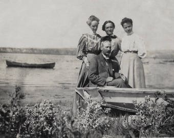 Old Photo Man and 3 Women By Lake Boat Long Skirts Man wearing Suit 1910s Photograph Snapshot vintage