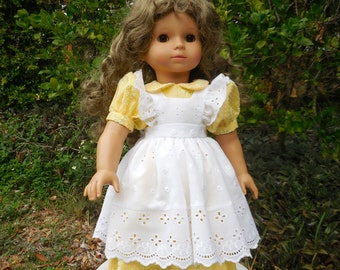 Yellow dress with a white, lace pinafore made to fit American Girl and similar 18 inch dolls.
