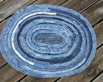 Denim oval throw rug. Great for any area. Made using the long seams from multiple pairs of recycled jeans. Frayed for a great unique look.