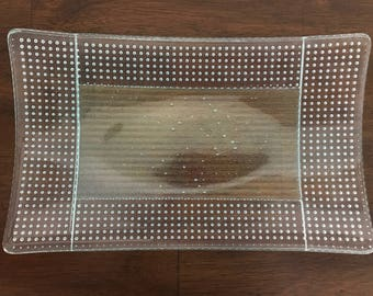 "Tray - Swoop form clear tray with linear pattern center panel and trapped bubbles in border. 11.5"" long by 7""wide and 1.25""deep"