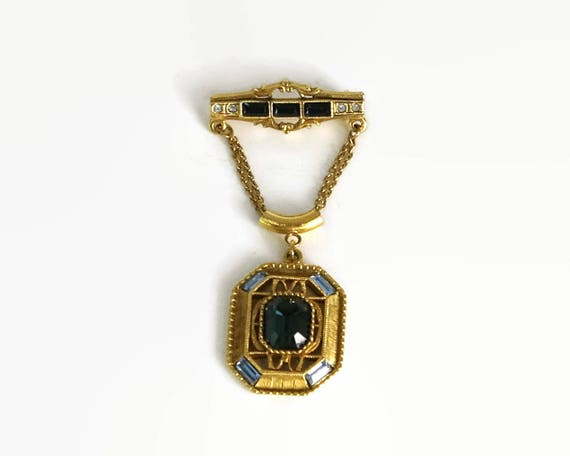 Vintage brooch, gold tone metal with blue crystals, octagon shape dangling from bar with fine gold chain, patterned back, mid 20th century