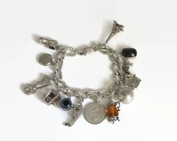Sterling silver bracelet with 13 charms, chunky curb link chain with mostly large charms, 7.5 inches / 19 cm, 55 grams, circa 1970s