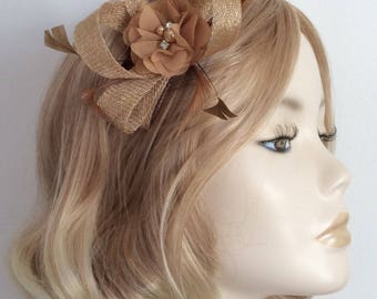 ALMOND GOLD FASCINATOR,  Made with sinamay,biot and coque feathers, chiffon flower, on a clear comb