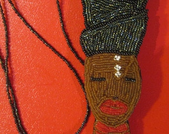 long embroidered necklace, depicting an African woman