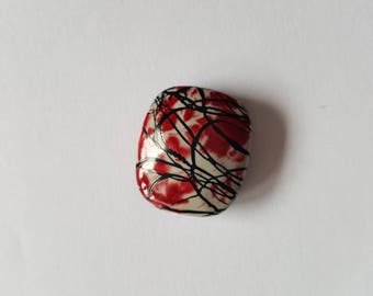 Rectangular red and beige acrylic bead.