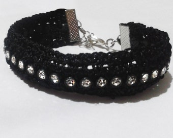 Handmade knitted bracelet in black color with decorative sparkle strass