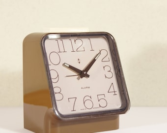 Space age clock. Made in West Germany. 70s of vintage mechanical alarm clock. Retro clock. Plastic / plastic, Brown. Europe 70s.