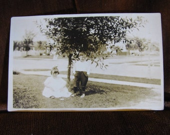 Vintage Real Photo Postcard in Sepia dated 1918 - 1930 Outdoors Young Children in Front Yard and Cute Clothes