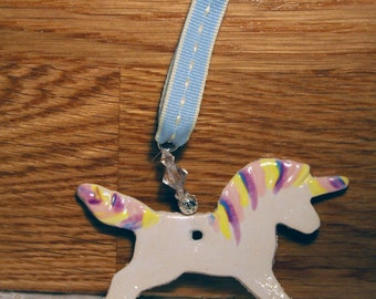 Rainbow Unicorn Pottery Ornament, with a rainbow mane glaze. Handmade pottery sent in a lovely gossamer bag ready to be given as a gift.
