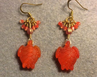 Orange red sea glass sea turtle bead earrings adorned with orange Czech glass beads and tiny dangling orange Czech glass beads.