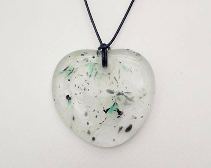 Green heart glass pendant, cast from transparent, green, grey, & black glass.