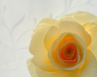 Large yellow paper rose, presented in a glass single stem vase.