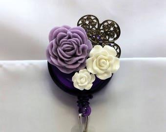 Purple and white flower badge reel