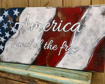 American flag, land of the free, rustic wood sign.