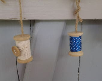Four large light wooden spools decorated