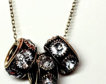 Three black, gold and crystal rondelles on a beautiful long chain