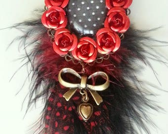 Red brooch with feathers