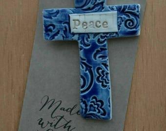 Handmade ceramic textured hanging memorial cross.
