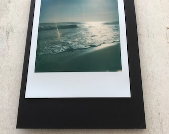 Blank greetings card with original polaroid photo of the sea