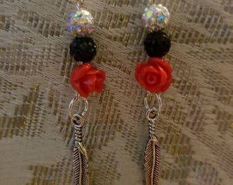 Red rose earrings with a white and black disco ball accent and silver feather charm