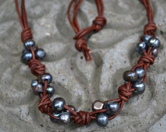 This is a beautiful necklace made with grey fresh water pearls and brown leather cord.