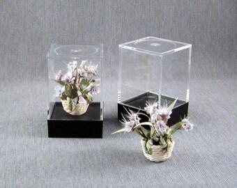 Light Lavender flower arrangement in a wicker basket all inside an acrylic showcase box