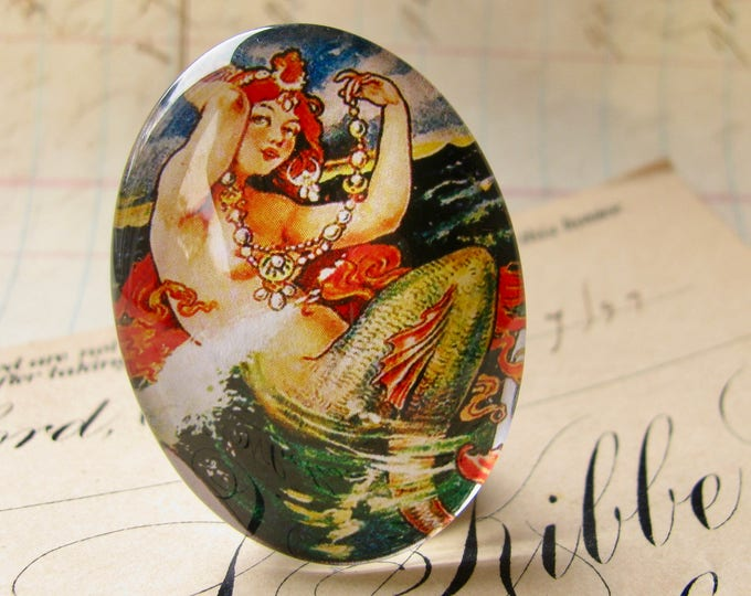 From our Magical Maidens collection, vintage mermaid comic illustration, red hair, 25x18mm glass oval cabochon, handmade in this shop