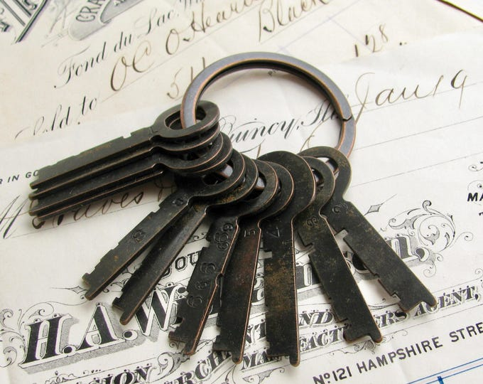 12 safety deposit box keys on a key ring, authentic keys, refinished black, 1.75 inches long, distressed, authentic vintage key