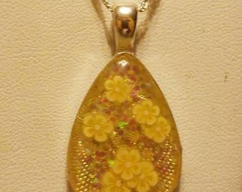 Lovely Little Yellow Flowers Floating Over Glitter in a Petite Teardrop Pendant.